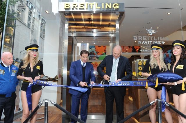 Breitling President Thierry Prissert and Travolta cut the ribbon